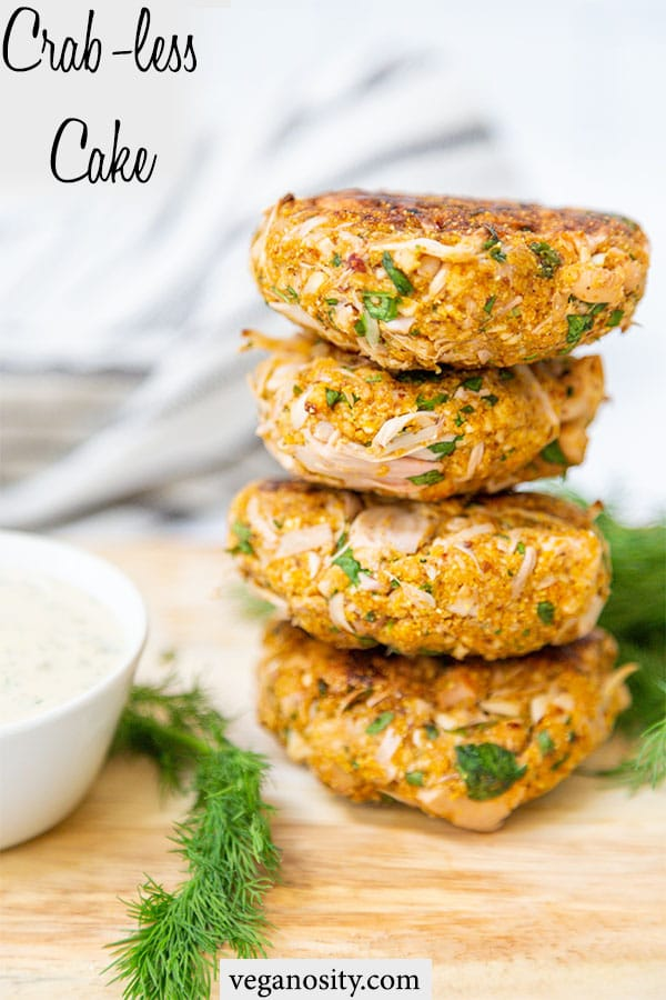 A Pinterest pin for vegan crab cakes with a picture of a stack of 4 cakes on a wood board.