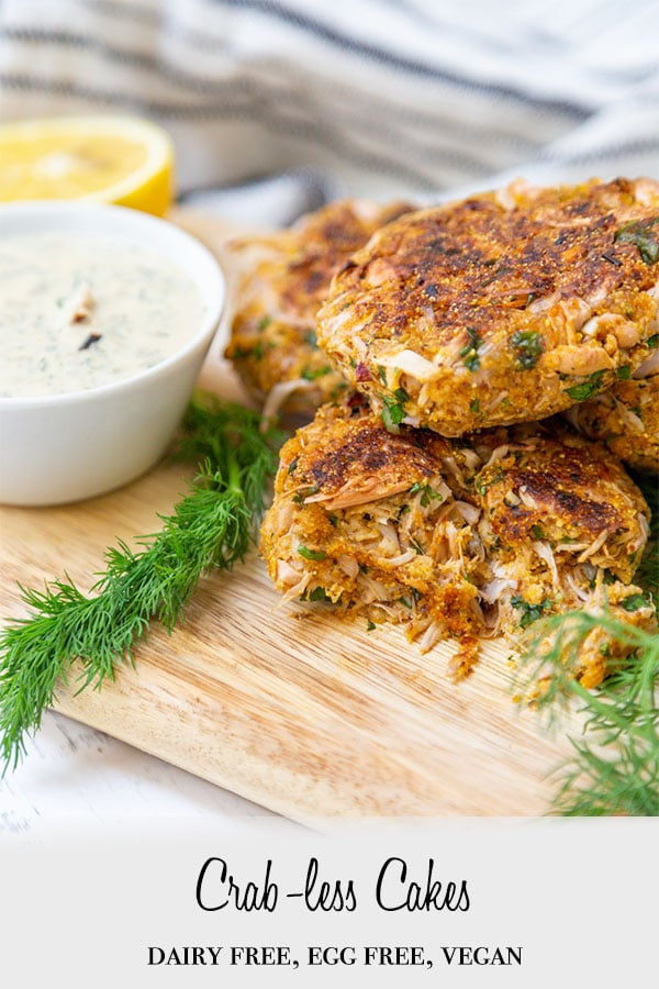 A Pinterest pin for Vegan Crab Cakes with a picture of a pile of the cakes on a wooden board with a bowl of tartar sauce and dill.