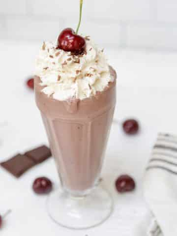 A chocolate milkshake in a tall glass with whipped topping and a cherry on top.