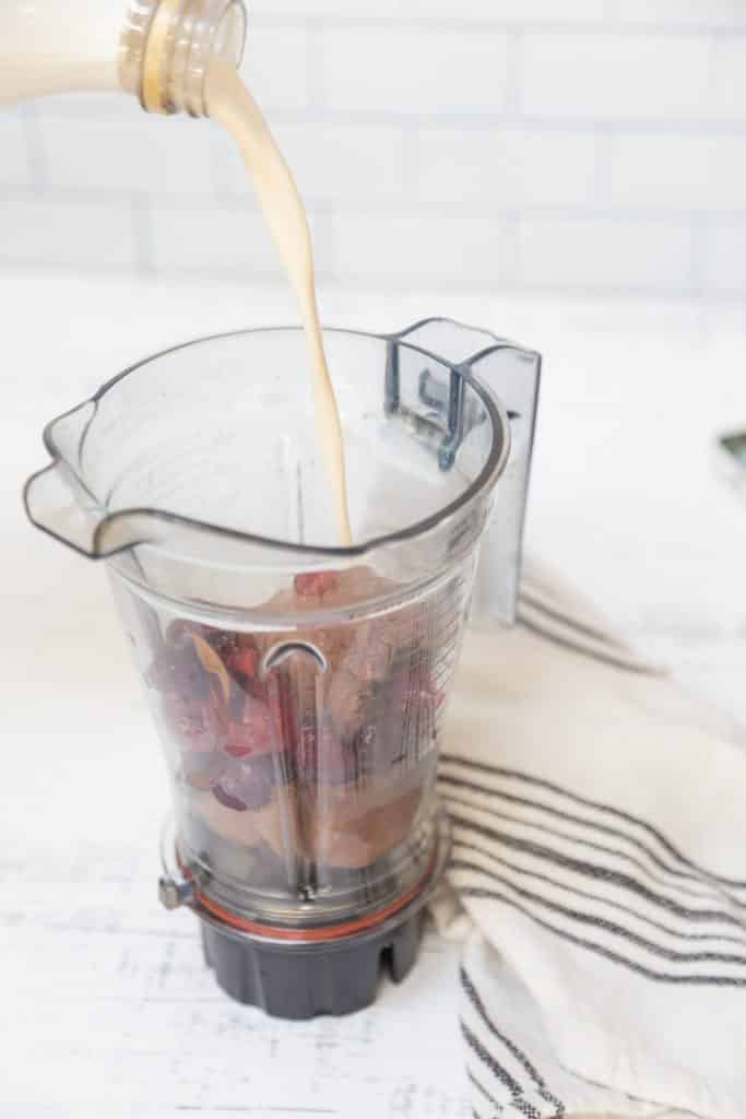 Milk being poured into a blender with chocolate ice cream and cherries.