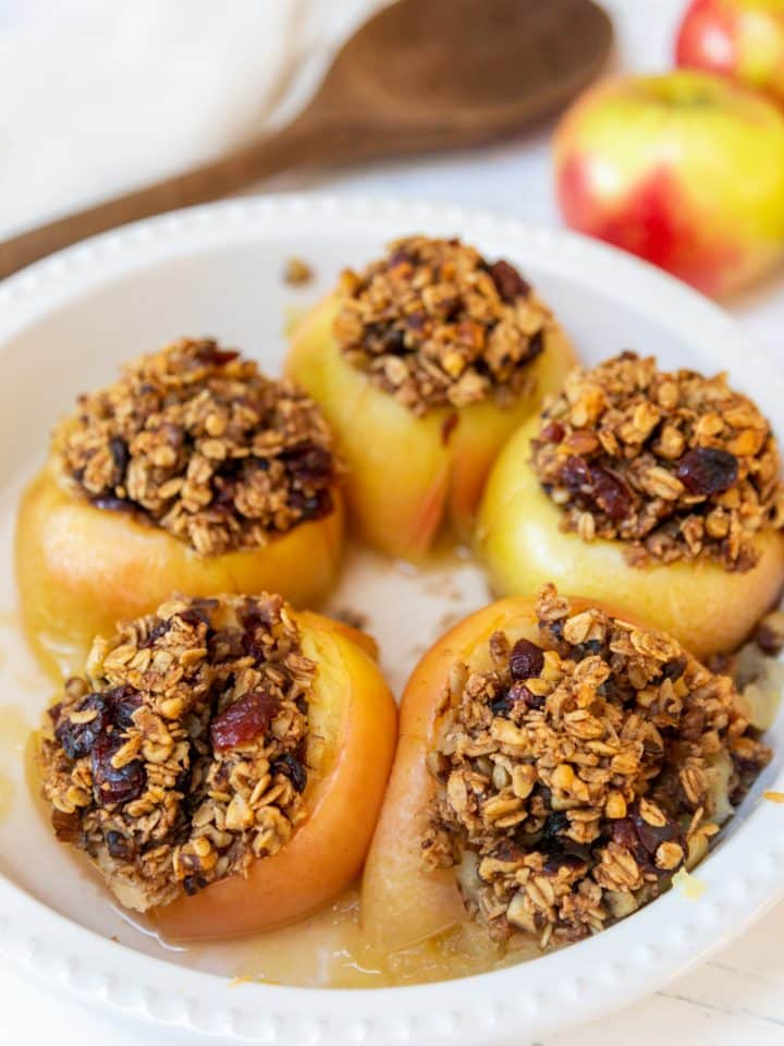 A round white baking dish with 5 stuffed baked apples and a wooden spoon and raw red apples in the background.
